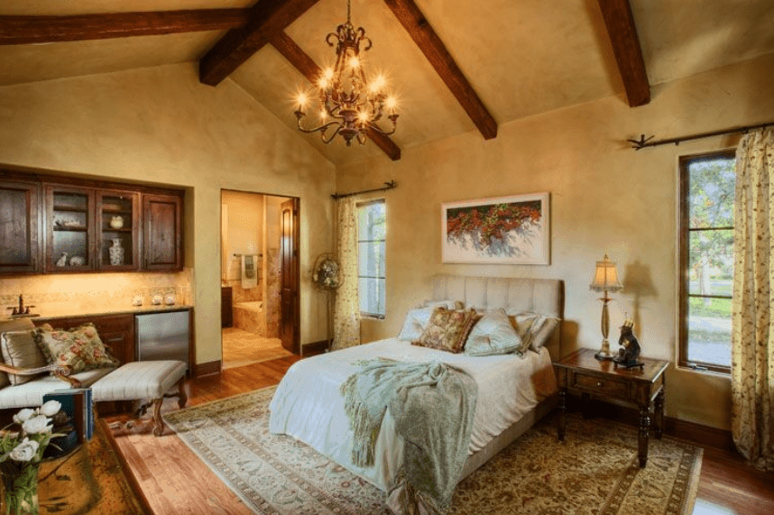 A traditional Spanish bedroom with beige walls and an elegant chandelier that lights up the arched ceiling and its exposed dark wooden beams. The dark wooden element can also be seen in the cabinets and the bedside table. The wall-mounted artwork above the headboard is a perfect addition to the details brought by the patterned carpet and curtains.