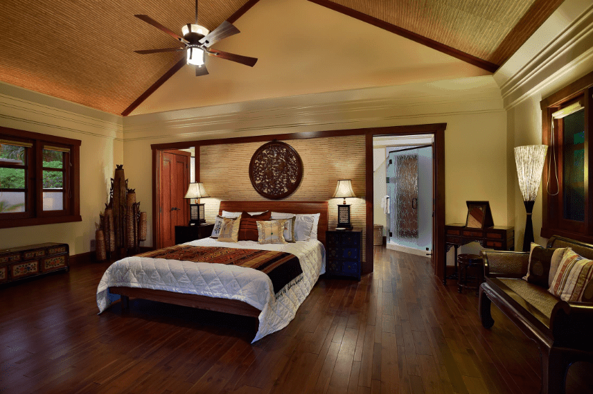 This is a warm and cozy Spanish bedroom that features different hues of wood. The wooden arched ceiling has the same striped pattern as the wall above the headboard where a wall-mounted dark wooden artwork dominates. This dark wooden element is also present in the wooden floors, side tables and even at the wooden sofa by the window.