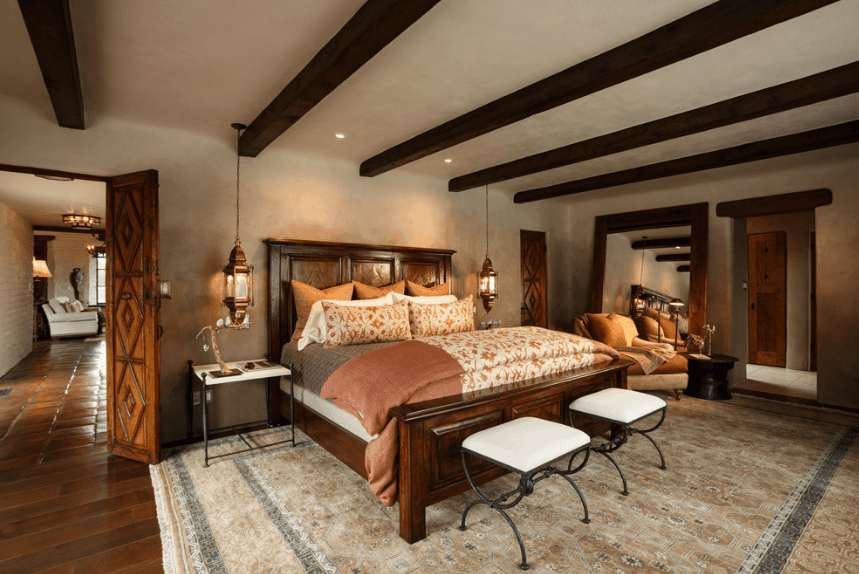 A cozy cottage-style Spanish bedroom that is mostly consisted of dark wooden tones and grayish white color. The dark wooden tones can be seen at various parts of the bedroom as the bed frame, floor, doors and exposed parallel wooden beams. A patterned grayish white rug spans across the floor from the bed to the reading area where a massive mirror with wooden borders leans against the wall.