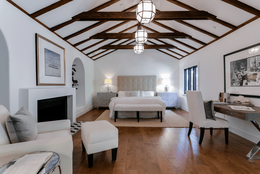 This is a predominantly white Spanish bedroom with white walls, white bed, white chairs, and a white fireplace. This allows the exposed dark wooden beams of the arched ceiling to pop out along with the wooden floor and legs of the pieces of furniture. The whole room is illuminated by three gorgeous hanging polygon lights.