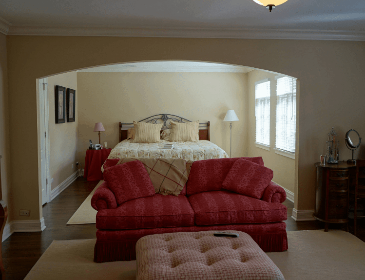 The beige walls and rugs of this Spanish bedroom give it neutrality that is contradicted by the stark color of the sofa by the foot of the bed and the linen covering the side table. The element that balances them is the dark wooden color of the floor, cabinet and wall-mounted frames together with the natural light of the windows.