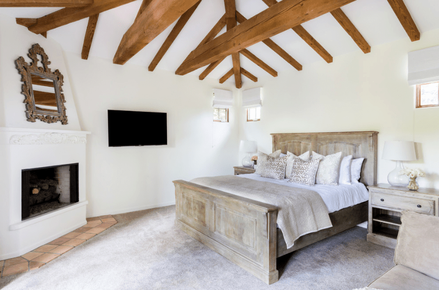 A simple and bright bedroom with light hues to complement the natural light. The distressed wooden finish of both the bed frame and bedside tables match perfectly with the grayish floor and muted bricks beneath the white fireplace. The dominating part of this Spanish bedroom is the arched ceiling where several exposed wooden beams form a pattern.