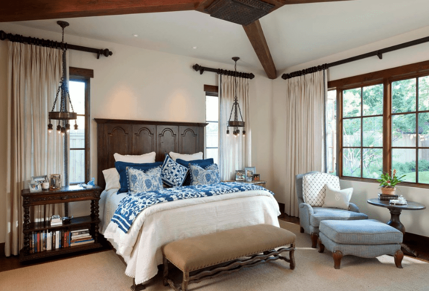 Two exposed wooden beams cross each other on the ceiling of this Spanish bedroom. This dark wooden element is also applied to the headboard, bedside shelves, window borders, and even the two hanging minute chandeliers that act as bedside lamps. A reading area by the french windows is a nice addition.