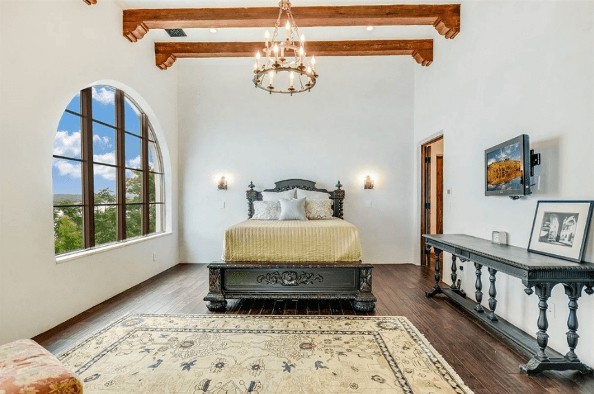 The stark white walls of this Spanish bedroom is a nice background to the beautiful dark wooden bed frame and traditional headboard which partners aesthetically with the console table at the side of the bed. The beauty of this room is further enhanced by the domed window and chandelier hanging from a ceiling with exposed wooden beams.