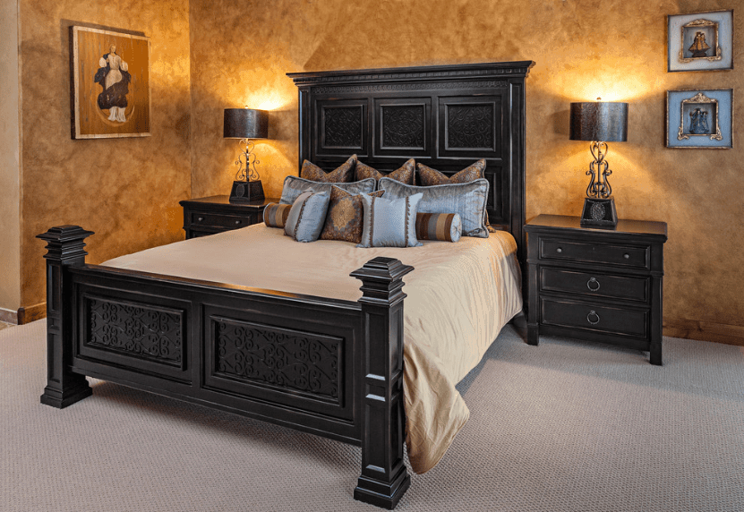 A very simple yet dramatic bedroom with a dark wooden bed frame that perfectly pairs with the bedside drawers and the dark lamps on top of them. The cloudy pattern of the wall and the monotone carpet offers a counterbalance to the wall-mounted religious artwork.