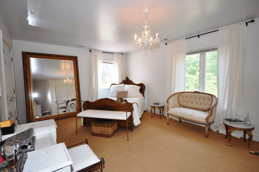 This is a bedroom of grandiose beauty due to its big spacious floor and grand mirror with brass borders that towers over the side of the bed. The white color of the walls and curtains give the room an illusion of being bigger it actually is. The brown element of the bed, side tables, and flour supplements this illusion.