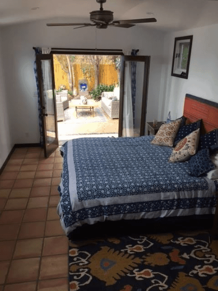 A small and accommodating bedroom that balances its lack of floor space with a door leading to the outside of the house. The brick-colored terracotta flooring also gives it an illusion of being wider while the patterns on the rug and bedspread provide character to the Spanish bedroom.