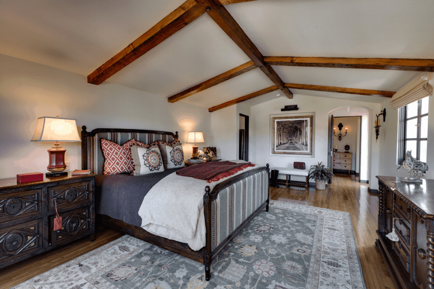 A wide, low-ceilinged bedroom with exposed wooden beams. It features a lovely wall-mounted scenery photograph at the side of the white bed with a dark wooden bed frame and gray striped headboard. This matches well with the light gray patterned rug and white walls.