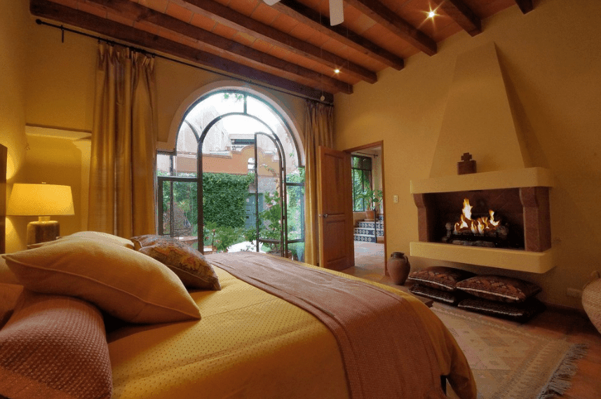 The almost golden hue of this room is complemented by the light coming from the elevated fireplace across the bed and the floor to ceiling glass doors leading to a garden. The exposed dark wooden beams of the ceiling provide a good contrast to the muted gold hue of the room.