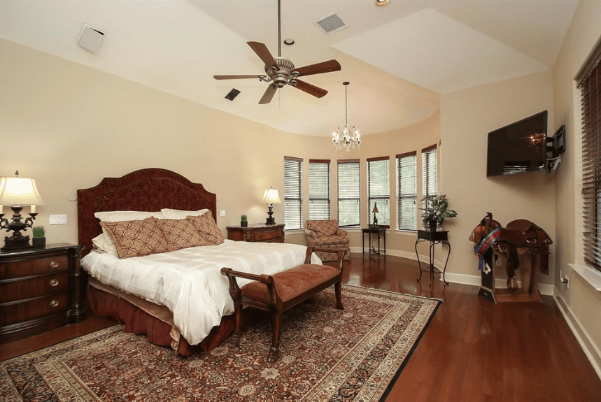 The eye-catching patterns of the headboard, pillows, single sofa and area rug transitions you towards the elegant solid colors of the dark wood floors, bedside drawers, and ceiling mounted fan. An addition of a reading nook within a rounded area filled with windows provides a cozy character to the Spanish bedroom.