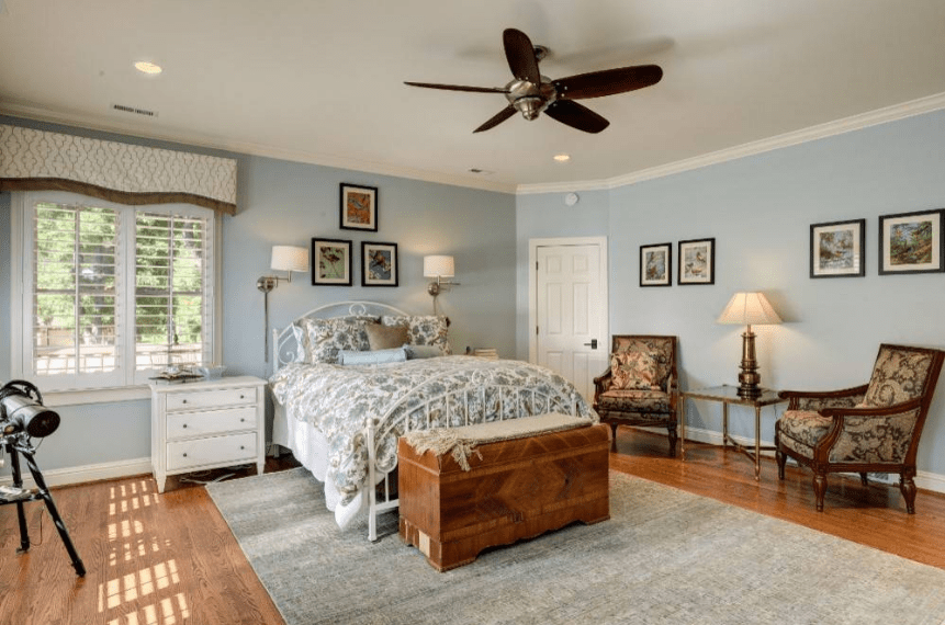 The patterns of the bedspread and single sofa chairs provide a cozy and traditional vibe to this Spanish style bedroom. However, it is balanced out by the modern wall-mounted lamps on either side of the bed and metallic table lamp at the side of the bed. The gray tone of the rug matches with the light hue of the walls which are peppered with wall-mounted photos.