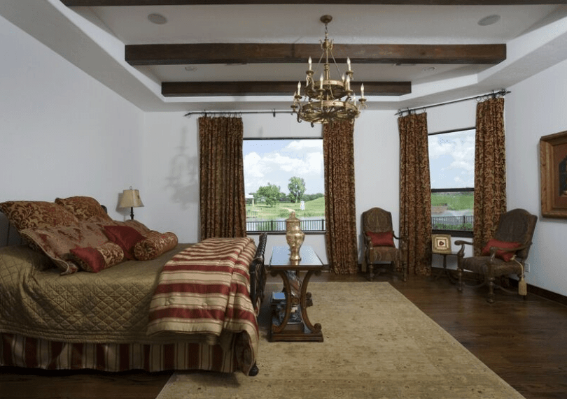 This bedroom is dominated by the chocolate brown hue of the wooden floors, exposed wooden ceiling beams, curtains, table, and French chairs. This is then contradicted by the red stripes of the bedspread, red pillows, and a majestic two-tiered golden chandelier.