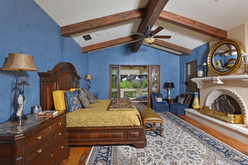 The blue walls, blue chairs, and blue patterned rug of this Spanish style bedroom complement the dark brown elements of the bed frame, bedside drawers, and exposed ceiling beams. Across the bed is a white fireplace with a semicircle alcove and golden fittings and above it is a peculiar circular mirror with golden borders.