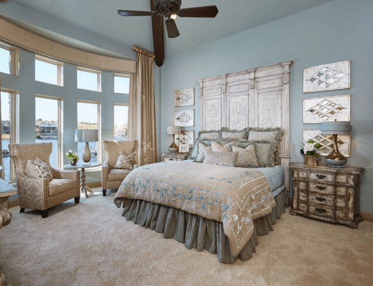 The light hue of the walls provides a good contrast to the silvery headboard that matches the modern wall mounted artwork on either side. The distressed bedside cabinets are an amazing touch that blends perfectly with the beige carpet and single sofa chairs in the reading area.