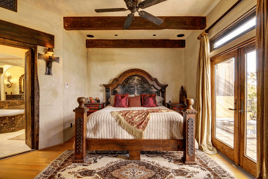 A small yet cozy semi-alcove bedroom that is dominated by a wooden bed with redwood bedside drawers. The wood elements are dispersed into the glass doorframe, door arch, and exposed wooden ceiling beams. The natural light coming from the glass doors illuminates the patterned rug in the middle of the room.