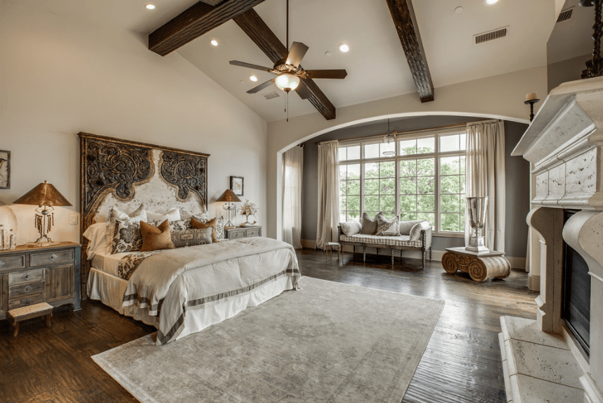 The dark wood floors and exposed ceiling beams of this elegant and airy Spanish bedroom is brightened by a massive window. The artistic headboard dominates one wall and pairs up with the two wooden bedside drawers while the fireplace with stonework lies across the bed.