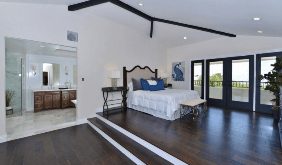 This is a stylish and spacious bedroom that highlights the dark wood with white color contrast. The dark wooden floors, exposed ceiling beams, bedside tables, and glass door boarders are all on full display. This makes the wall-mounted art, blue pillows and even the bench at the foot of the bed pop out aesthetically.