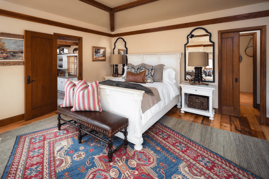 A cozy Spanish bedroom that features patterns over print design. This is emphasized on the colorful patterned rug over a plain gray rug and even the patterned pillows on the plain white bed that matches with the two white bedside tables. A lovely addition of the two mirrors behind the two bedside lamps completes the complexity of this room.