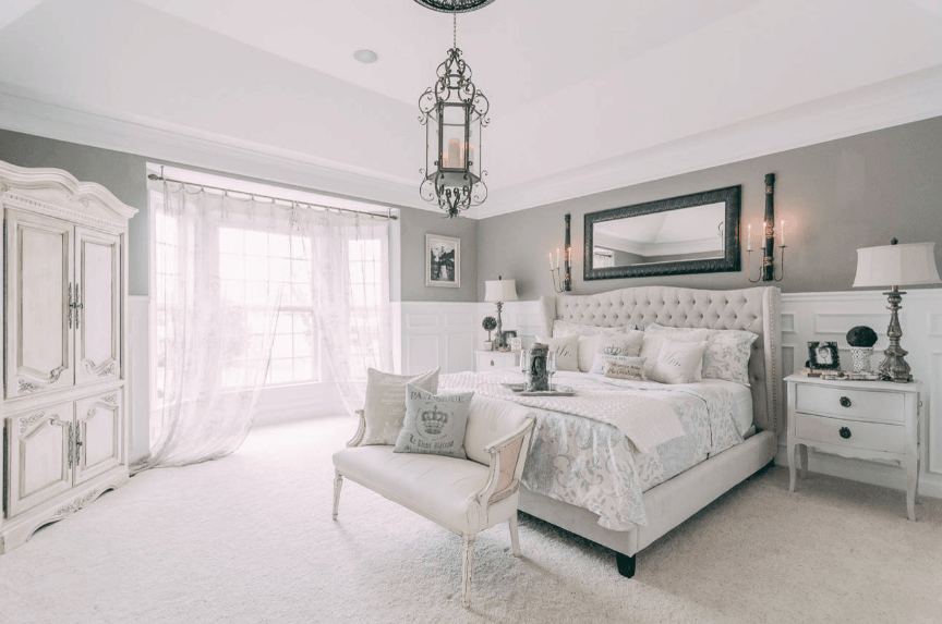 The centerpiece of this room is the ornate Victorian pendant lighting that matches with the wall mounted mirror and lamps above the cushioned headboard. The gray and white walls share its hue with carpeted floor, bedside drawers and the large wardrobe at the corner of the room. The two silver bedside lamps complete the ensemble.