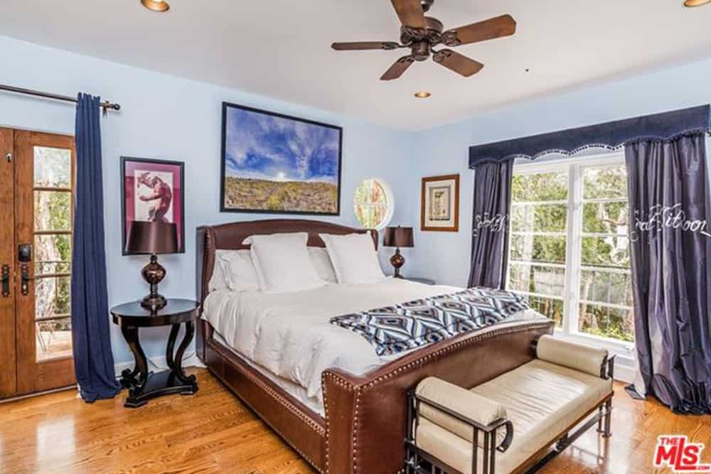 This bedroom exudes style and sophistication from its leather bedframe that matches with the two round bedside table. This is a good dark contrast to the lightness of the wall and the large window at the side of the bed. This room also features a peculiar round window near the headboard that blends well with the wall-mounted art.