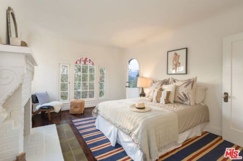 The blue striped rug in the middle of the room catches the attention first in this Spanish bedroom. It then gently transitions you to the elegant details of the room like the white fireplace across the bed, wall-mounted art above the bed and the large french windows.