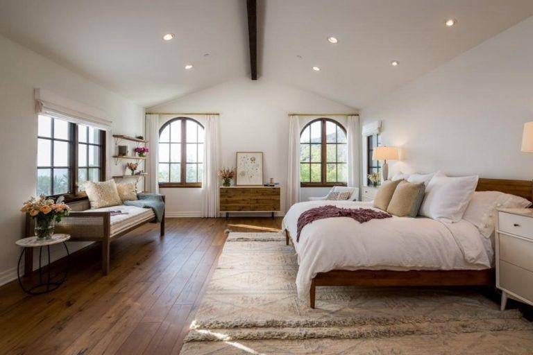 This Spanish bedroom is airy, spacious and offers a lot of light sources from the four windows to the several pin lights of the arched ceiling and a pair of bedside lamps. The single exposed wooden beam in the middle of the ceiling is a nice touch as well as the reading area with a wooden sofa beside one of the windows.
