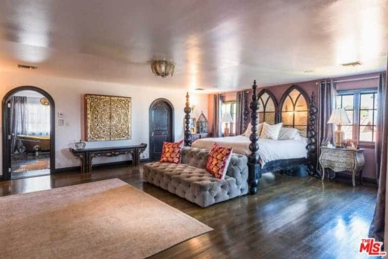 Immense Spanish master bedroom features a huge wooden four-poster bed with elegant bead patterns at the posts. Instead of a headboard, it has a pair of Gothic-shaped windows that offer a great view of the sunset. The dark wooden floor is a great partner for the distressed side tables and brass details that are peppered across the room.