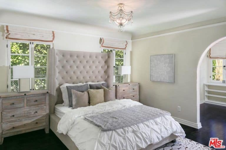 This is a Spanish style room with transitioning colors from the dark wood floors to the grayish brown of the bedside drawers and bedframe then finally to the whiteness of the bedsheets, walls, and ceiling. The addition of a stylish crystal semi-flush mount lighting caps off the whole room with a sophisticated touch.