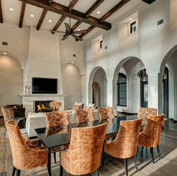 This is a Spanish dining room that shares its high-ceiling and exposed beams with the living room. There are stone pillars and arched walkways on one side leading to the wooden floor. The modern glass-top dining table is surrounded by patterned velvet upholstered chairs.