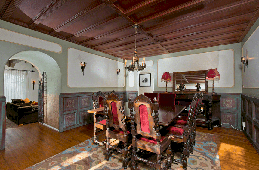 This traditional Spanish dining room has a dark wooden coffered ceiling with a small hanging iron chandelier. The dark wooden table with matching wooden chairs is well-rooted to tradition. On the other hand, this tone is balanced by a colorful patterned rug that pairs with the light hues and pattern of the wall finishing.