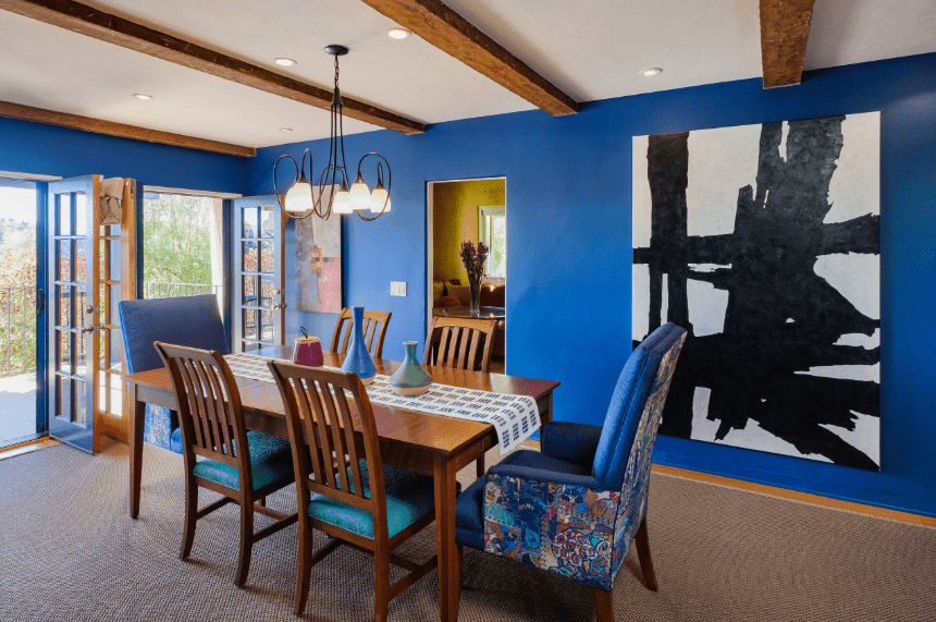 This is a predominantly blue Spanish dining room with its blue walls, French doors, and cushions on the chairs surrounding the wooden table. This is then contrasted with wooden hues from the exposed ceiling beams, table, and slat-backs of the chairs. The stark contrast is mediated by the simple chandelier, wall-mounted artworks, and grayish carpeted floor.