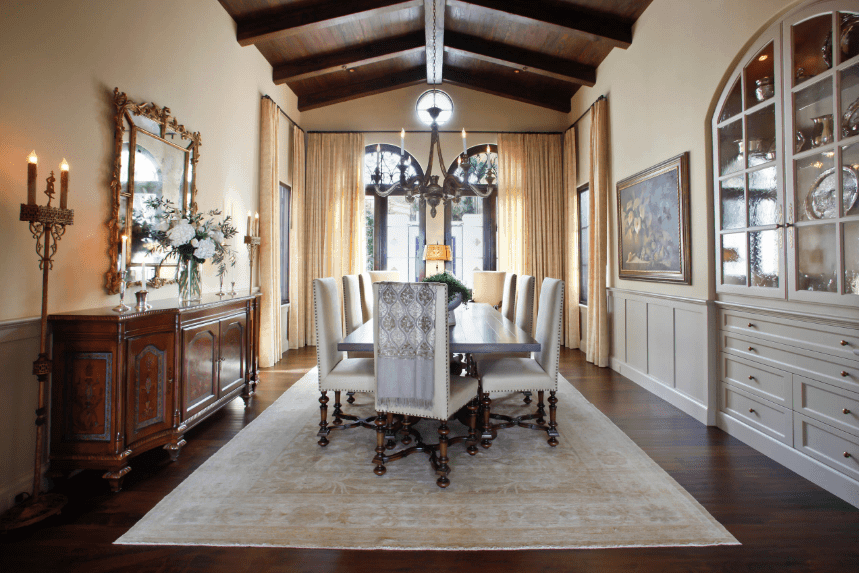 The earthy tones of the dark wooden floor and cathedral ceiling with exposed beams are balanced by the white walls, built-in French cabinet, and rug in the middle of the room. The large wooden table and Parsons chairs share this combined theme of wood and white. These are all brilliantly illuminated by the glass doors and the hanging curved chandelier.