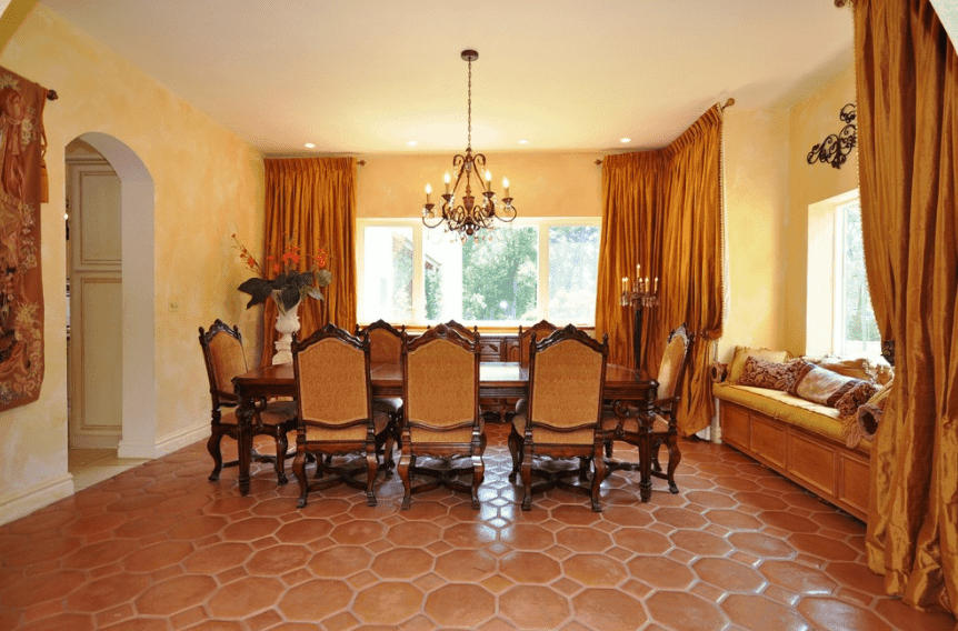 Warm yellow light bathes this room coming from the elegant hanging chandelier that is further enhanced by the beige walls and golden curtains. The pin lights at the corners of the ceiling also help to add to this effect. The bergère chairs and rectangular wooden table paired with the terracotta floor give this Spanish dining room an old-world feel.