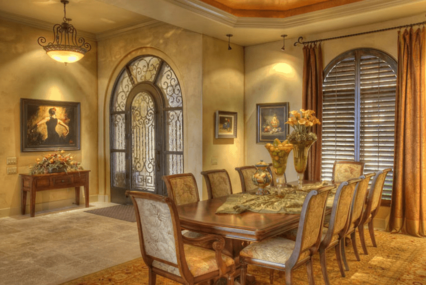 This traditional dining room appears to be taken out of a painting with its patterned rug and warm yellow lighting. The wall-mounted paintings are quite elegant and match well with the ornate patterns of the wrought-iron door and cushioned wooden chairs. The wooden table serves as a background to the beautiful centerpieces and shuttered windows.