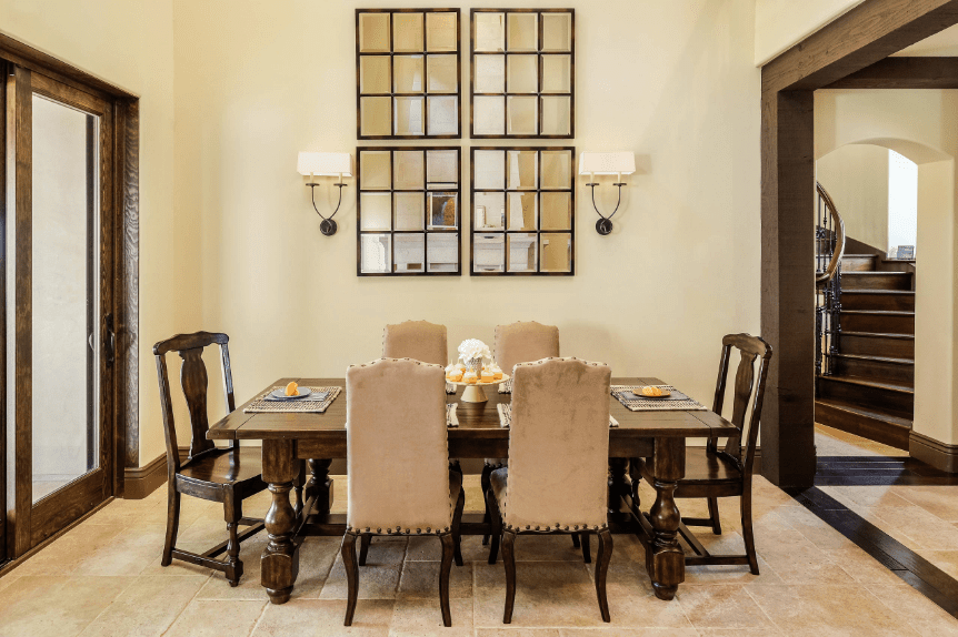 A simple and elegant dining room that is dominated by a set of four wall-mounted modern mirrors flanked by two lamps. Serving as accent are the wooden tones of the wooden beam walkway, glass door boarders and dining table and chairs. The white textured floor contrasts with the smooth white walls and completes the aesthetic.