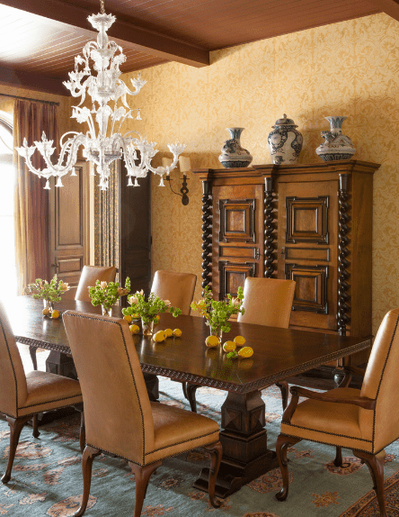 The intricate white chandelier gives contrast to this room that is dominated by the dark wooden tones of the ceiling with exposed beams, dining table, upholstered chairs, and French cabinet. The light hues of the patterned area rug reflect the vase display and patterned walls.