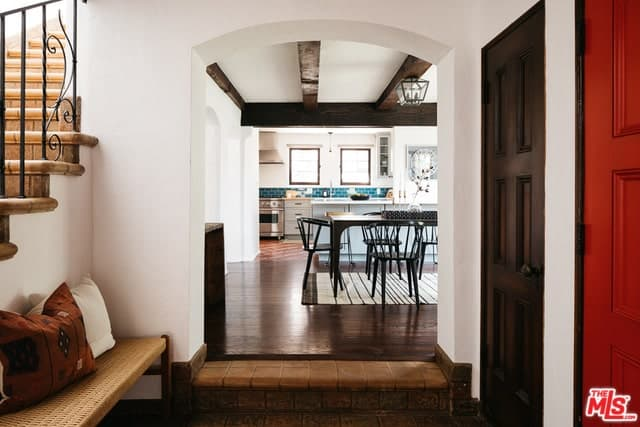 This Spanish foyer has a rustic brown wooden floor that has a distinctive difference to the floor of the next room giving it a gradual transition from the exterior to the interior of the house. The white walls are accentuated with the arched entryway and dark colored doors. The addition of a woven bench caps off the rustic vibe.
