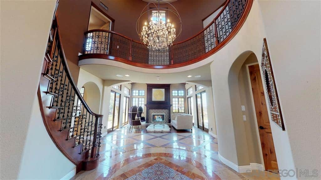 This is a Spanish foyer with a nice view of the fireplace, a high ceiling and a marble floor that has a patterned detail in the middle. This pattern on the floor is a wonderful reflection of the majestic chandelier that has a modern spherical design. The beige walls wonderfully contrast the dark wooden details of the staircase and railings.