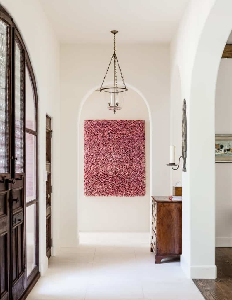 A lovely pink wall-mounted artwork gives a vibrant depth to the foyer. It makes the white of the walls seem brighter and the wooden tones of the door and drawer darker. There also some brilliant details that stand out against the monotony of wood and white like the frosted glass of the main doors, wall-mounted candelabra, and a hanging glass pendant light.