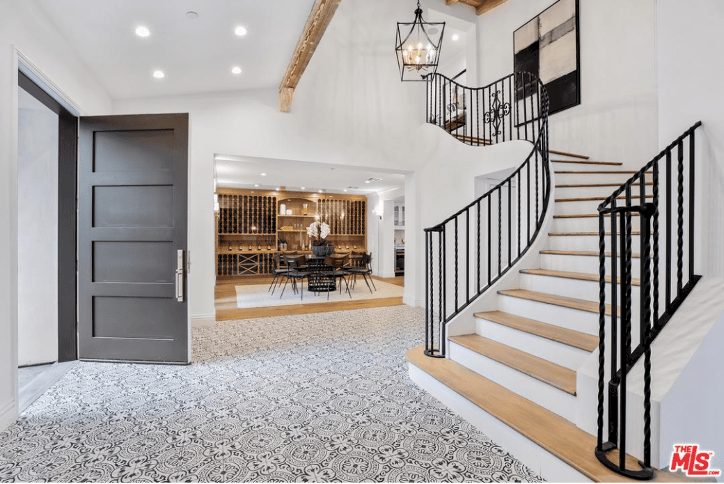 The patterned floor tiles of this Spanish foyer is a wonderful contradiction to the pure white walls and ceiling with a single wooden exposed beam. This beam has the same hue as the steps of the staircase while the black iron railings are the same as the hanging pendant lantern light from the high ceiling.