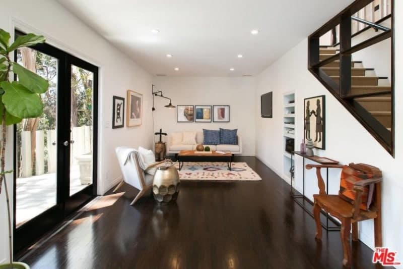 The polished dark wooden floor is a perfect pair for the frames of the glass double doors and staircase railings. This is then balanced by the white walls, ceiling, and bright pin lights. A bit of personality is given by the modern console table and brass stool that is combined with a traditional armed chair and wall -mounted artwork.