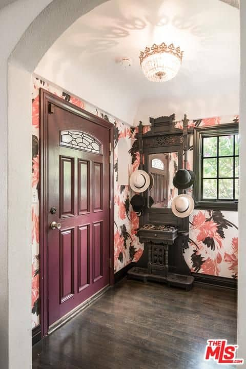 The play of colors in this Spanish foyer makes up for its lack of floor space. A purplish wooden main door partners up with a dark wooden apparatus that serves as a hat rack, shoe rack, and mirror frame. It wonderfully contrasts the floral wallpaper and elegant flush mount ceiling light.