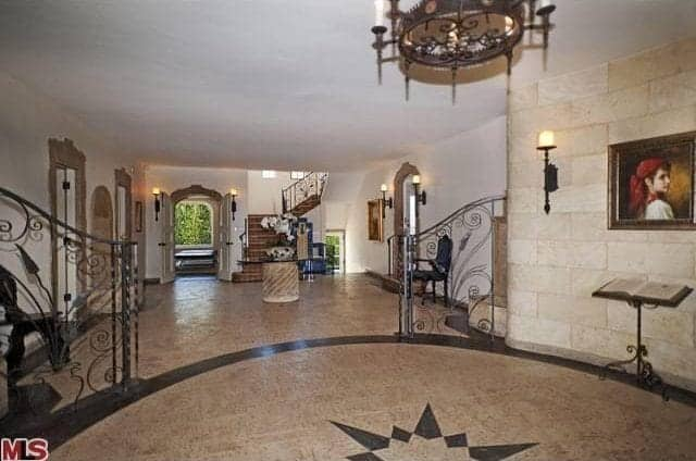 This is a spacious and circular foyer with a star-like pattern on its marble floor. This coincides well with the traditional dark chandelier from the low ceiling and wall-mounted lamp. This room is decorated by a book stand with an open book beneath a painting mounted against marble walls.
