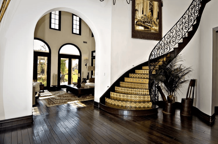 A feel of elegant tradition exudes from this white-walled Spanish foyer. The deep brown hues of the wooden floor and spiraling staircase stands out against the white walls. The patterned tiles of the stairs and beautiful tapestry hanging by the stairs solidifies the aesthetic.