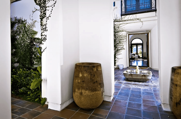 This is an outdoor foyer with a terracotta floor. It makes the white walls starker against the big wooden urns placed at corners of the entryways. The stand-out element is the small fountain near the middle of the floor. This adds a bit of traditional elegance to this simple foyer.