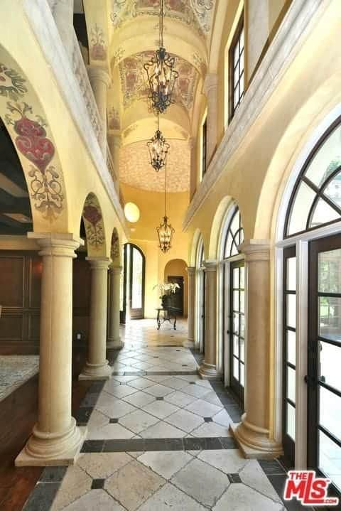 This foyer has a high groin vaulted ceiling that has painted art which makes it seem like a church cathedral rather than a foyer. The stone pillars, French glass doors, and traditional hanging pendant lights further enhance this theme. The floor is a good reflection of the French doors where ample natural light illuminates everything.