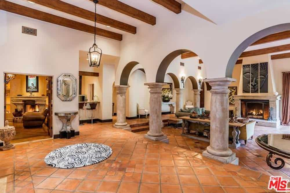 This spacious foyer has a lot of different elements that somehow work together beautifully into an eclectic fusion. There are terracotta floors paired with a zebra print rug. There are marble pillars paired with exposed wooden beams of the white ceiling. And to cap it all off, white walls are paired with a modern half-circle console table beneath a silver octagonal mirror.