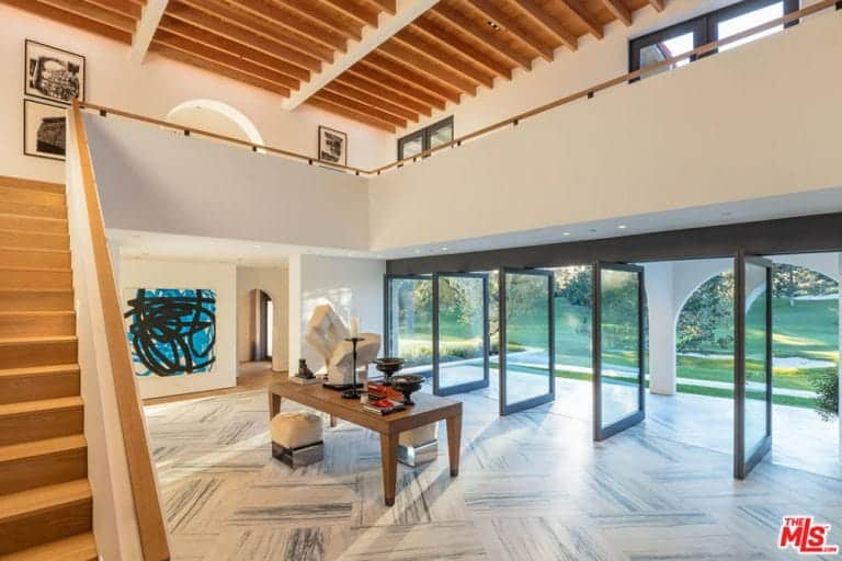 Massive glass pivot doors mark the entrance to this wide and airy Spanish foyer. The marble floor extends from the interior to the outside almost seamlessly. In the middle is a large wooden display table with artworks that breathe in the natural light. The white walls and high ceiling with wooden exposed beams make this room seem bigger.