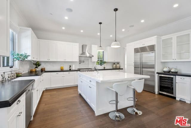 This Spanish-style kitchen has a wide white ceiling with recessed lights and a couple of white pendant lights hanging over the white kitchen island. This is then contrasted by the dark hardwood flooring and the black countertop of the large L-shaped peninsula.