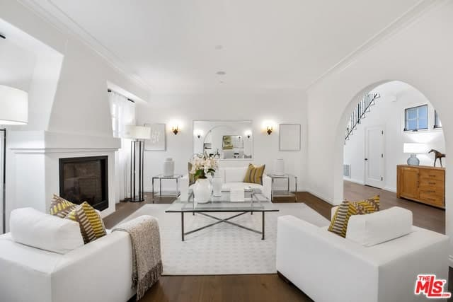 White living room with a pop of yellow from the pillows adding color to the space. It features a fireplace facing the huge center table surrounded with white sofa and chairs.